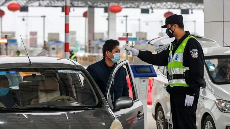 A traffic police officer measures the temperature of drivers in Wuhan (China)