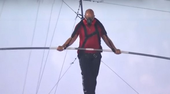 The acrobat walked on a cable over the crater of an active volcano